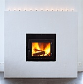 White, projecting masonry fireplace with tea light holders on mantelpiece and burning fire