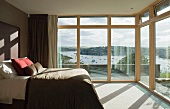 Bedroom with glass wall and view of river