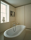 Bathroom with free-standing bathtub and bust on windowsill