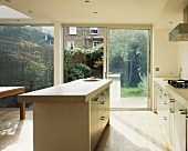 Sunny kitchen with island and glass wall leading to terrace