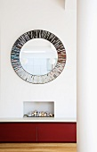 Large, round mirror hung above built-in fireplace