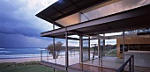 Contemporary, steel and glass house on coast with dramatic clouds