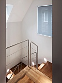 View of stairwell with modern wooden staircase and stainless steel balustrade