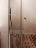 Tiled shower area with wooden slatted floor