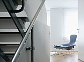 Open door in stairwell with view of classic armchair and footstool