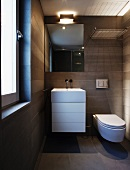 Grey tiled, designer bathroom with washstand and base unit next to wall-mounted toilet