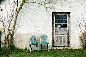 Two wooden chairs against exterior wall next to weathered door