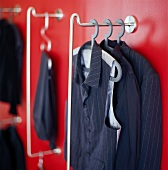 Men's clothing on coathangers against red wall