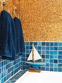 Small sailing boat on rim of bathtub