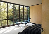 Bedroom with armchair and footstool in front of glass wall