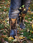 Legs with jeans and wellies in autumn garden
