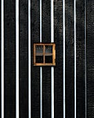 Black and white wooden wall with small window