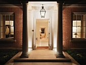 Illuminated entrance with open door and view of hallway