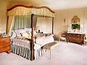 Antique four-poster bed with canopy in traditional bedroom