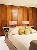 Bedside lamps on head of double bed in front of wooden fitted wardrobes
