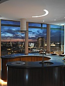 Circular kitchen unit in penthouse apartment with panoramic view of city skyline