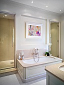 Bathtub with white-painted wood panelling in renovated bathroom