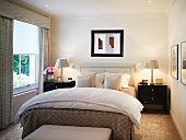 Light bedroom with black bedside cabinets and white bedside lamps
