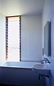 Corner of modern, white-tiled bathroom with bathtub below window with tilted glass slats