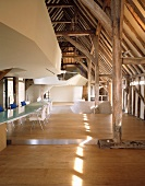 Roof structure in converted historic building with long, modern glass table next to glass wall