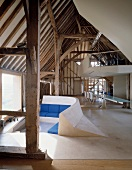 Deconstructivist installations in historic roof structure - sunken seating area with blue upholstery in front of panoramic window
