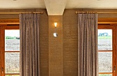 Small, modern wall light between wooden windows with curtains on wooden poles