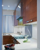 Modern, U-shaped fitted kitchen with wooden doors, stainless steel elements and white work surfaces