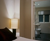 Lit bedside lamp and taupe walls in modern bedroom with ensuite bathroom