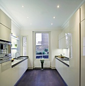 Modern fitted kitchen with glossy, cream doors in London apartment in old building