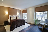 Bedroom with Roman blinds on large windows, modern double bed and antique armchair