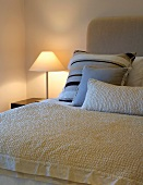 Scatter cushions and bedspread on double bed next to lit bedside lamp