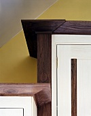 Wooden kitchen cupboards with white-painted doors and dark frames