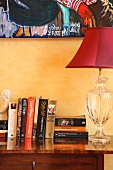 Books next to red lamp with decorative glass base on antique chest of drawers