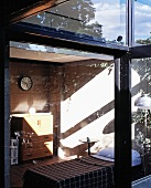 View of sunny bedroom with unrendered walls though glass facade with wide sliding doors
