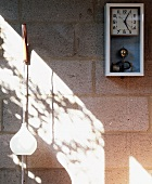 Retro wall clock and pendant light on unrendered concrete block wall