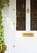 White, antique front door with stained glass windows and brass letterbox