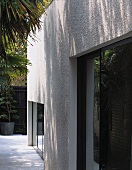 A modern stucco facade with dark window elements