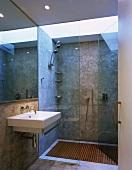 Designerbad mit Oberlicht über bodengleicher Dusche mit Holzrost und grossformatigen Fliesen