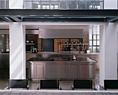 A stainless steel designer kitchen with an island cooker and an industrial atmosphere