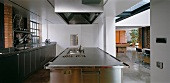 A spacious stainless steel kitchen leading onto a loft-style living room-cum-dining room