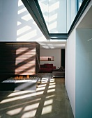 Pattern of light and shade in open-plan room with fire burning in futuristic fireplace open on all four sides