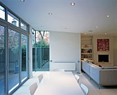 Open-plan, modern room with sofas and dining area in front of wide glass wall