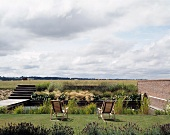 Wooden deckchairs in garden bordered by river with view of open landscape
