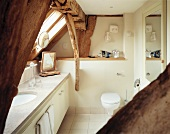 Low-ceilinged, cream bathroom with marble washstand below exposed roof timbers and slanting windows