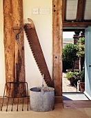 Antique farmyard implements in front of half-timbered beams and open door leading to garden