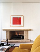 Red picture and modern fireplace with stone surround in white, panelled wall