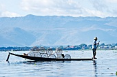A man on a rowing boat on Inle Lake in Mayanmar (Burma)