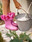 Woman with flowery Wellington boots filling a bucket with water