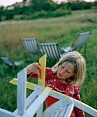 Mädchen beim lackieren eines Stuhles