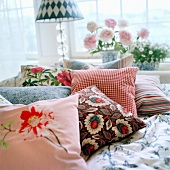 Several scatter cushions on patterned bed linen